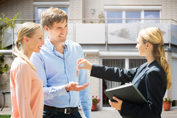 Real Estate Agent Giving House Key To Couple