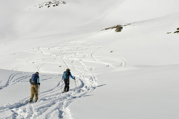 Background: young man and woman, sporty, walking with snowshoes in fresh snow, high mountains, sunny, cold day, following path, head towards peak, winter, shadow, Alps, Valais, Simplon Pass, Swiss