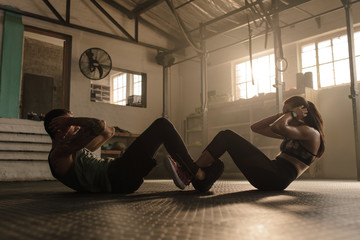 Couple doing sit-ups together in gym