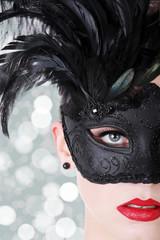 Hübsche Frau mit Federn Maske und rotem Lippenstift