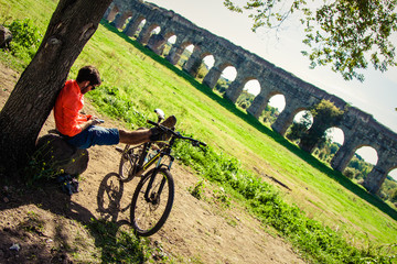 Backpacker sitting on a rock under a tree with feet on his bike using smartphone in front of ancient roman aqueduct. Young attractive athletic man with orange sportswear and backpack in acquedotti