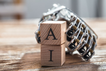 Robot's Hand Holding Wooden Blocks With A And I Alphabet