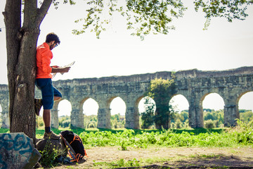 Backpacker standing on a rock under a tree reading a map in front of ancient roman aqueduct. Young attractive athletic man with orange sportswear and backpack in acquedotti park in Rome