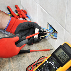 Electrician technician working safely on a residential electrical system.