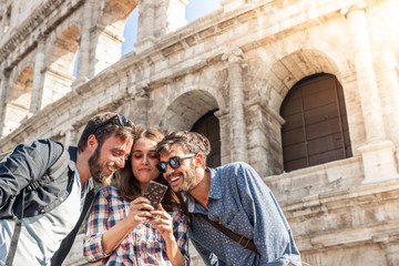 Three happy young friends tourists at Colosseum in Rome using smartphone having fun on sunny day. Lens flare.