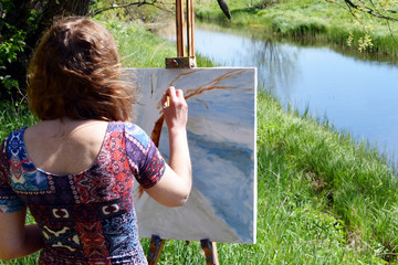 Rear view of artist paints a beautiful summer landscape with river. Painting on canvas is not ready.