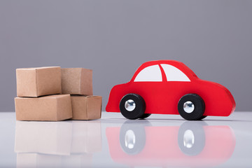 Red Car And Cardboard Boxes On White Desk
