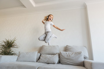 smiling kid jumping on sofa and listening music with headphones