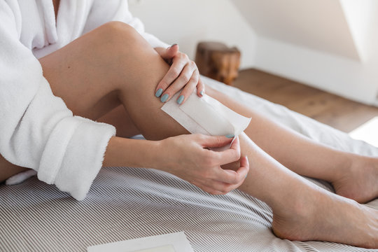 Unrecognisable woman waxing her legs at home.
