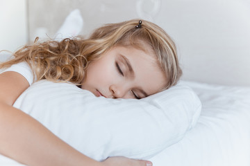adorable kid sleeping on pillow in bedroom