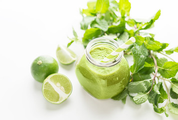 Green healty drink in mason jar with green fresh mint and lime on white background. Vegetarian food concept. DetoxText space
