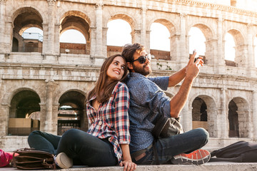 Happy couple sitting in front of colosseum in rome taking selfie pictures with smartphone camera. Sunset with lens flare.