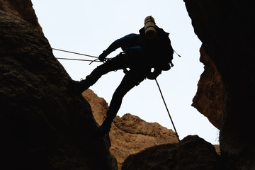 Climber silhouette abseiling down from a rock cliff.