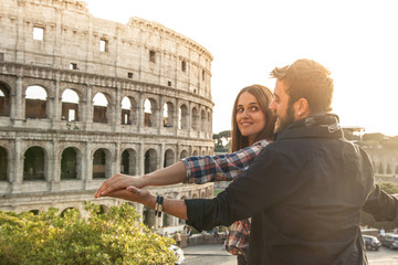Romantic young couple tourists doing iconic TITANIC scene in front of colosseum in rome. Boyfriend holding girlfriend spreading arm. Sunset with lens flare.