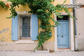 Colourful house wall facade, yellow wall and light blue doors and shutters, Provence village, south France