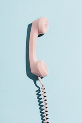 Pink telephone on a blue background.