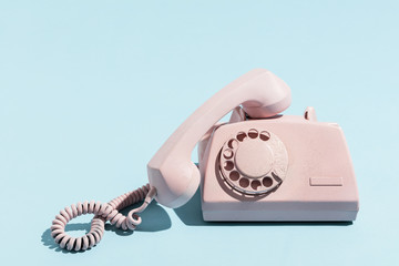 Oldschool pink telephone on a blue background
