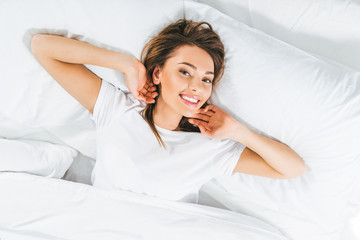 top view of beautiful smiling girl relaxing in bed