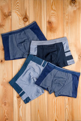 set of cotton panties for boy clothes on wooden boards top view