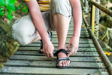 tourist corrects the clasp at the Sandals on the trail