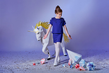 Pretty girl in an elegant blue dress for teenage girls with a make-up. Origami and minimalism. Fashion kid.