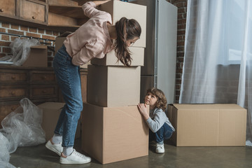 happy mother and son playing with cardboard boxes in new apartment