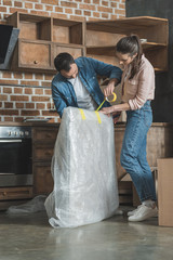young couple packing picture while moving home