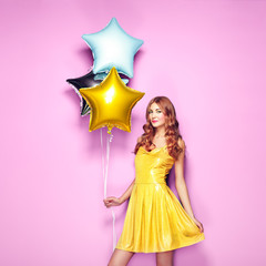 Beautiful young woman with colorful balloons on a pink background. Birthday and party. Girl in yellow dress at the festival. Valentine day