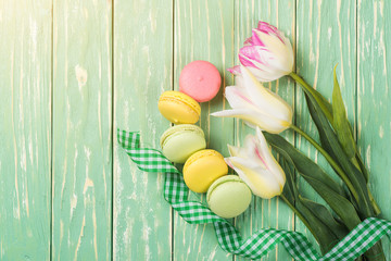 Colorful macaroons and beautiful bouquet of tulips on the wooden background. Top view. Copy space.