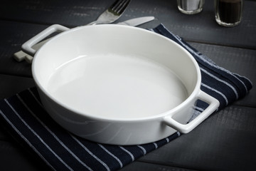 Empty dish for baking on a dark countertop.