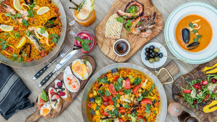 Assorted spanish food set. Tapas, Paella, grilled seafood, olives, seafood soup, strawberry lemonade, grilled scallop on wooden table