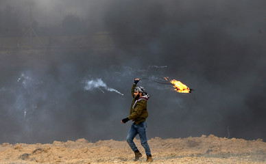 Palestinian demonstrator holds a fire during clashes with Israeli troops, near the border with Israel in the southern Gaza Strip