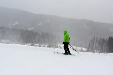 Young woman skier on a steep snowy slope, winter blizzard in the mountain, Aleko Ski Resort, Vitosha Mountain, Bulgaria