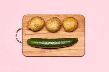 Healthy Eating. Three Fresh Potatoes Near Cucumber On A Wooden Chopping Board