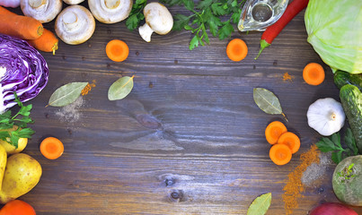 wood background with vegetables, spices and oil