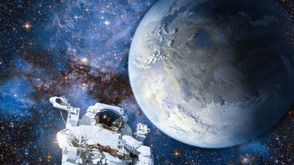 Astronaut in outer space against colorful storm galaxy and earth. (Elements of this image furnished by NASA)