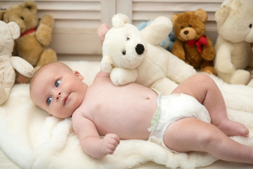 Baby lying on white duvet. Baby boy with teddy bear
