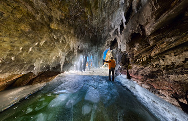 Panorama man in an ice cave with icicles on Baikal, Olkhon