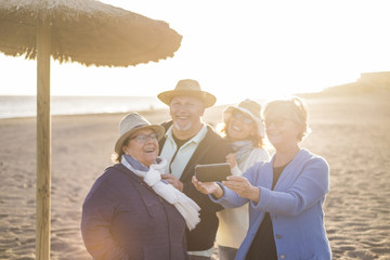 group of friends, elderly and middle age, having fun at the beach
