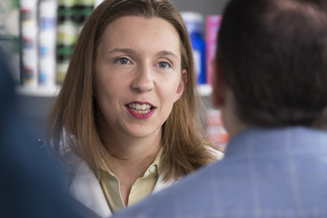 Portrait of a pharmacist talking with male customer