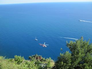 Elicottero in volo lungo la costa con mare e imbarcazioni