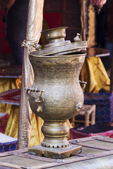Arab old brass kettle over an old travel trunk