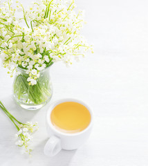 Bouquet of Lilies of the Valley and   cup of tea    on white wooden  table.