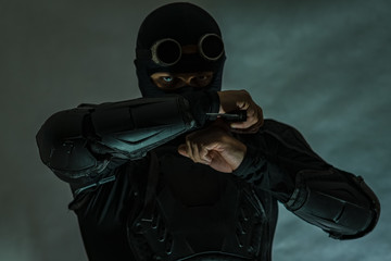 Armed spy in bulletproof vest. Masking glasses. A military knife is prepared for a strike.