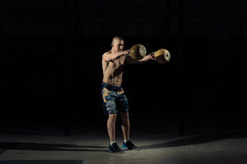 A strong man picks up kettlebell in gym. Sportlife
