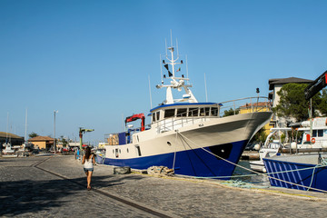Summer. Italy. Cesenatico. Museum of the ships. The boat is white and blue. Embankment.