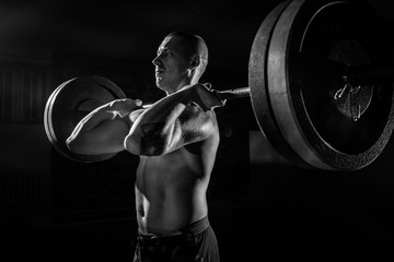 An athlete lifts a barbell on his chest in the gym. bw. sport
