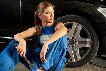 Pretty female mechanic sits near the wheel of black car. Girl is dressed in work uniform and holds a wrench in her hands. In the wheel you can see the key for removing the wheel