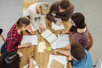 Group of people cooperating at table in office