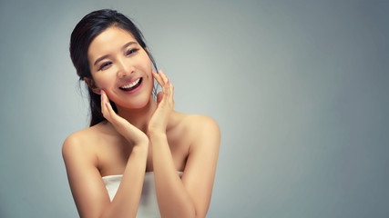 Happy beautiful asian girl with the fresh skin in grey colour background. Expressive facial expressions. Cosmetology and Spa concept.